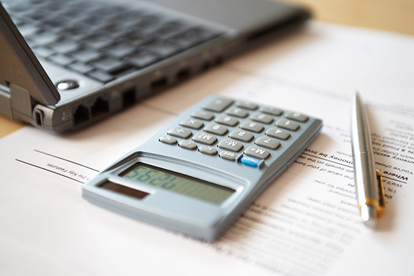 laptop and calculator on tax and financial documents